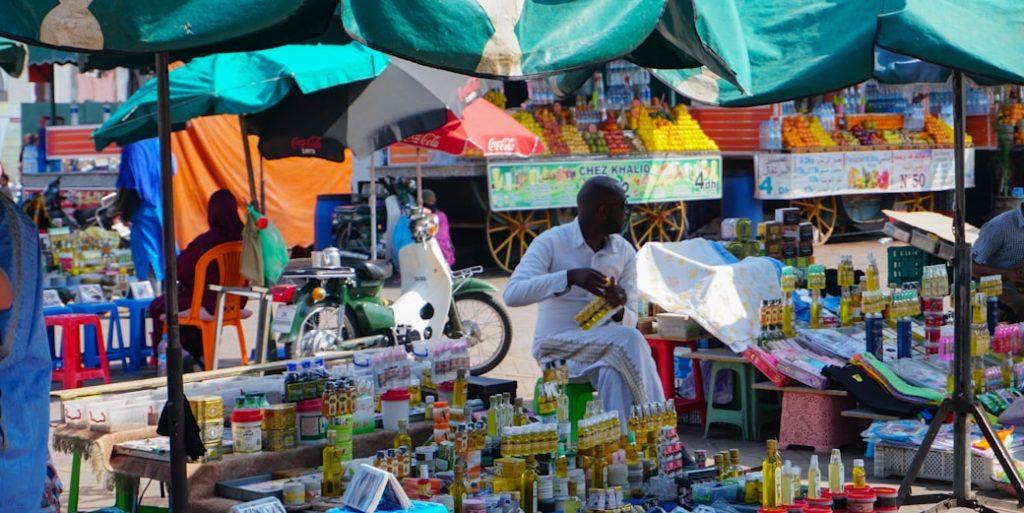 Pan sprzedający olejki arganowe, w tle stragany sprzedawców soków, Marakesz